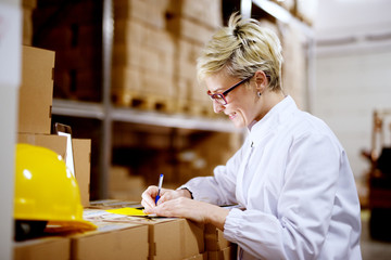 Young beautiful happy female worker is filling a paperwork on a stack of cardboard boxes while smiling in factory storage room.