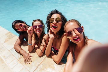 Group of friends taking selfie photo in pool.