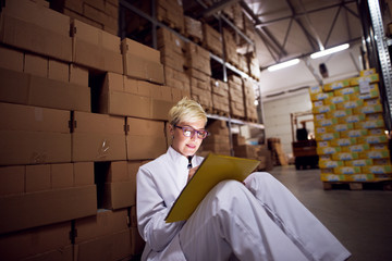 Young beautiful focused female worker is filling a paperwork on the yellow folder that is leaned against her lap while sitting on floor leaned against a stack of brown cardboard boxes.