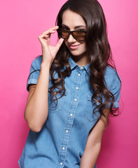 Stylish young woman with long beautiful hair and adjusts her sunglasses