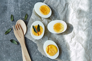Boiled eggs for breakfast with wooden fork and spoon decorated with green leafs on grey table