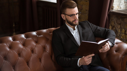 Confident handsome bearded businessman in a smart suit and glasses reading a book or check the reports on the work of sitting on the couch in the office.