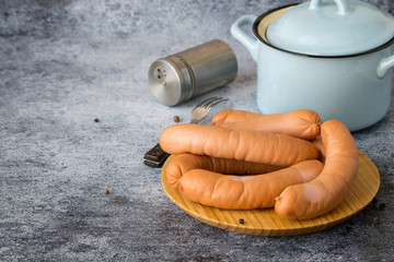 Fresh veal sausages on a round wooden board, next to a small saucepan and a metal jar with spices on a blue background with copy space.