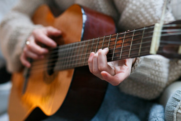 Play the guitar by hand Artist or musician.Young woman hands in knitted sweater. Home music party