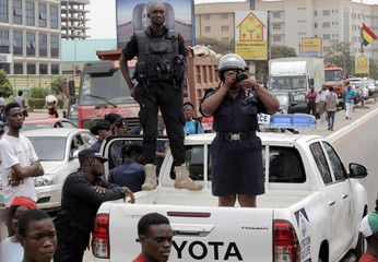 Police officers stand on a pick-up truck as one of them takes pictures during a protest in Ghana's capital Accra against the expansion of its defence cooperation with the United States