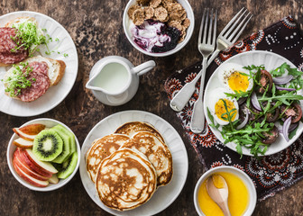 Greek yogurt with whole grain cereals and berry sauce, pancakes, arugula, cherry tomatoes, boiled eggs salad, kiwi, apples fruit, salami and cream cheese sandwiches on a wooden background, top view