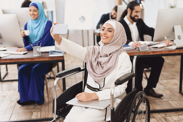 Disabled arab woman in wheelchair working in office. Woman is taking selfie.