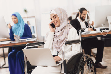 Disabled arab woman in wheelchair working in office. Woman is working on laptop and talking on phone.