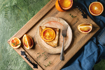 Homemade crepes pancakes served in ceramic plate with bloody oranges and rosemary syrup with sliced sicilian red oranges on wooden tray over green texture background. Top view, space
