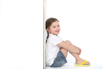 Hübsches kleines Mädchen mit Flip Flops sitzt an einem Kasten und lacht