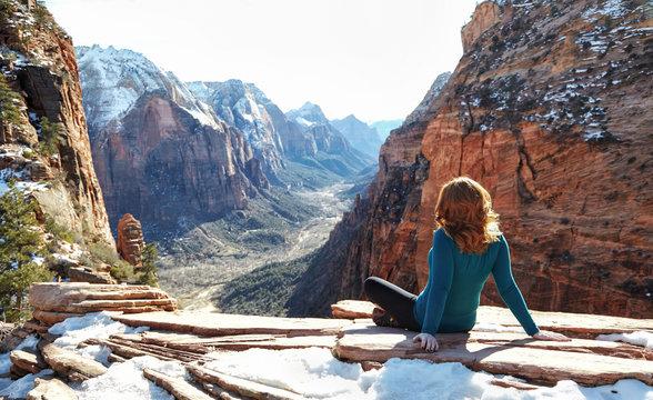Redhead woman enjoying mountain view while sitting on rocks