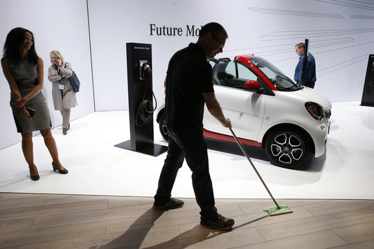 Worker sweeps near Smart car at the New York Auto Show in New York