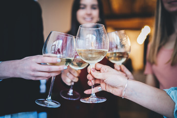 Happy friends making cheers with glasses of champagne in modern loft, group of people celebrating and toasting at cozy home atmosphere, togetherness and traditional concept