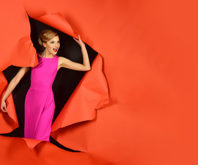 Beautiful sexy blonde girl in pink dress emerging through ripped red paper. Surprised woman with perfect makeup, red lips, open mouth, breaking paper background.Copy space for advertise clothing store