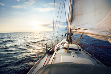 View from the deck to the bow of a sail yacht tilted in a wind on a sunset