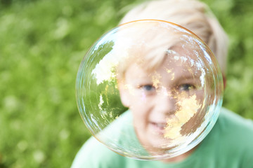 Young boy blowing bubbles with greenery background. Selective focus.