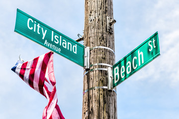 City Island Avenue and Beach street signs at intersection in Bronx, New York City, NYC with american flag