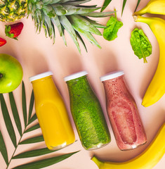 Flat-lay of colorful smoothies in bottles with fresh fruits on pink  background, top view. Natural Organic Food Style.