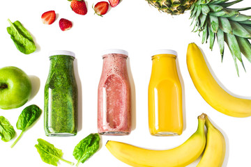 Flat-lay of colorful smoothies in bottles with fresh fruits and berries isolated on white background, top view. Natural Organic Food Style.