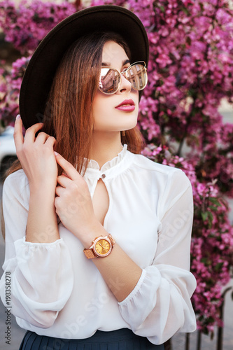 a75b937ef2e Outdoor close up portrait of young beautiful fashionable girl posing near  blooming tree. Model wearing stylish golden wrist watch