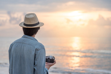 Young Asian man traveler and photographer with jean shirt and hat holding film camera and looking beautiful sunset at tropical beach island. Summer holiday or vacation travel concepts