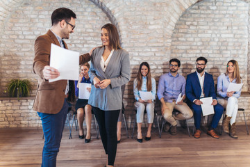 Businessman shaking hands with woman besides people waiting for job interview in a modern office