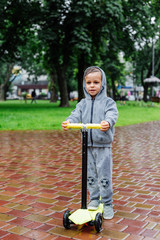 Drenched in the rain, a boy in a sport suit skates on a scooter. Spring walk in the city park, rainy weather.