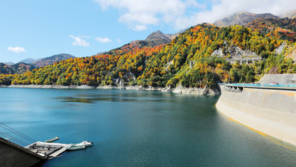 Scenery of autumn lake with boats parking by lakeside and mountains of colorful foliage by Kurobe Dam in Tateyama Kurobe Alpine Route, Japan