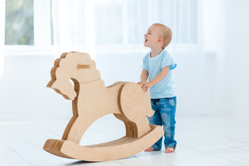 Cute, smiling, white, two years old boy in blue t-shirt and jeans rocking on wooden handmade horse....