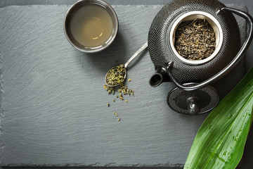 Green japanese tea on black slate. Black teapot with dry green tea. Tea preparation. Top view with copy space.