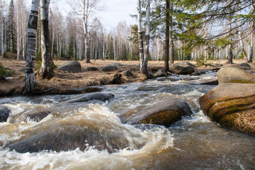 A river with a fast current. In the river big stones