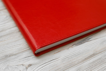 Photo book with embossing. Photobook on a light surface. Red photo book with  leather cover. Photoalbum with a hard cover on a wooden background. Bright red photo album.