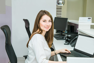 Portrait of smiling skilled administrative manager working on laptop with white empty screen in office satisfied with occupation, young female receptionist. Selective focus, space for text.