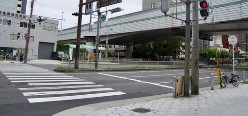Osaka City Center - Quiet grey cityscape of a residential part of downtown city center Osaka in Japan (Asia) with houses, a crosswalk, traffic lights and a bridge