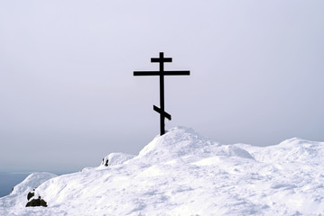 orthodox cross on top of the mount Konzhakovskiy Kamen against the background of the surrounding winter mountains..