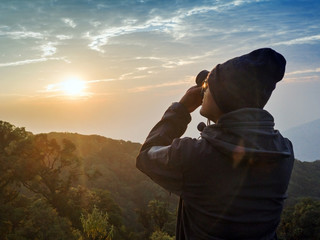 Back of Asian Man Shooting Photo Scene Sunrise with beautiful sky at Chiangmai Thailand.