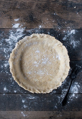 not perfect homemade pie shell with fork marks on dark wood surface sprinkled with white flour flat lay