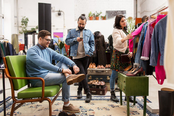 sale, shopping, fashion and people concept - friends choosing clothes and footwear at vintage clothing store