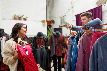 sale, shopping, fashion and people concept - couple choosing clothes at vintage clothing store and showing thumbs down