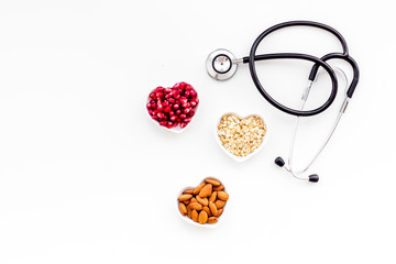 Proper nutrition for pathients with heart disease. Cholesterol reduce diet. Oatmeal, pomegranate, almond in heart shaped bowl near stethoscope on white background top view copy space
