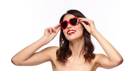 valentines day, beauty and people concept - happy smiling young woman with red lipstick and heart shaped sunglasses over white background
