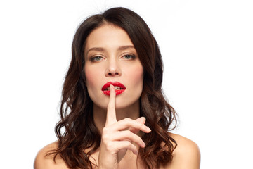 beauty, secret, make up and people concept - woman holding finger on lips or mouth with red lipstick over white background