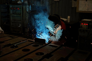 The welding welder is engaged in the manufacture of parts welding with sparks.