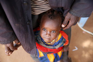 An Ethiopian girl stand next to a man in line for registered as a refugee by the UNHCR in the Dambala Fuchana refugee camp near the Ethiopian-Kenyan border town of Moyale