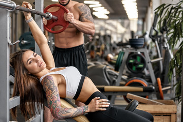 Personal trainer helping woman working with heavy dumbbells