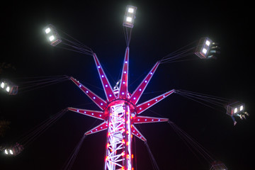 funfair ride spinning round at night with legs dangling down