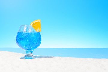 Refreshing blue drink with ice and a slice of orange in a glass on the sandy coast