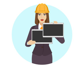 Businesswoman in construction helmet holding a two digital tablets PC
