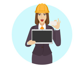 Businesswoman in construction helmet holding a digital tablet PC and showing business card