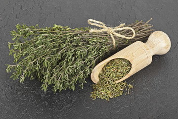 Dried thyme and bundle of thyme sprigs on black background